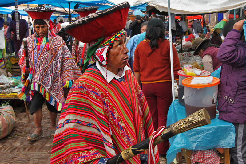 Quechua dancers in traditional dress walk through the Pisac market in the Sacred Valley of Peru