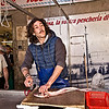 Fish monger prepares fresh-caught seafood at the daily morning market in Syracuse, Sicily.