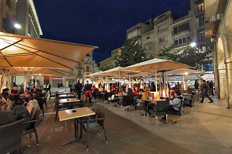 Shoppers at Christmas Market in Figueres, Spain take a break for dinner at outdoor cafes