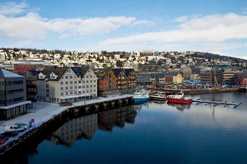 Prim buildings are mirrored in the in glassy waters of the harborfront inTromso, Norway