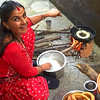Nepali Woman makes fried Sel Roti rice flour rings over an open fire during the Hindu holiday of Tihar in Pokhara, Nepal