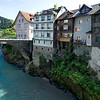 "Heiligkreuz bridge leads to houses built on a rocky outcropping aside the River Ill in the ""Im Kehr"" area of Feldkirch, Austria"