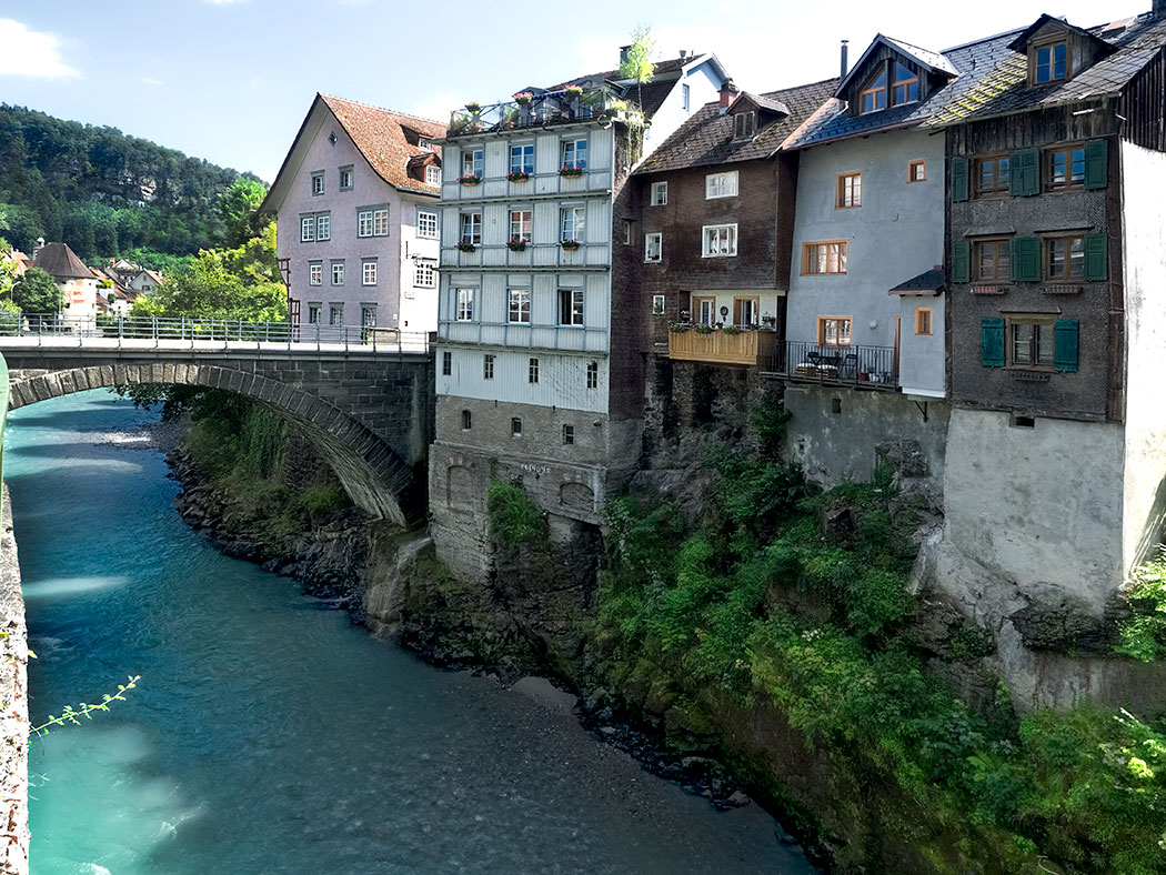 Heiligkreuz bridge leads to houses built on a rocky outcropping aside the River Ill in the