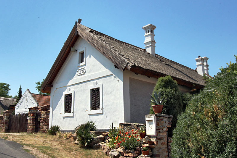 Hungarian peasant version of Classical stone cottage with thatched roof, whitewashed walls, and plaster carvings, in the Kali Basin