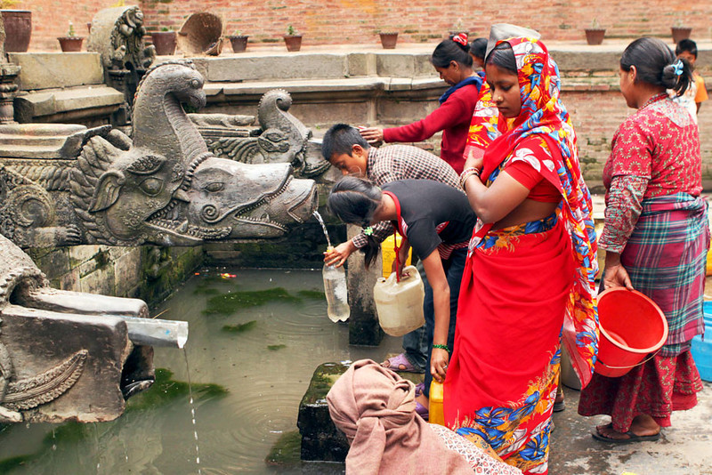 Collecting fresh water at a fountain in the historic Durbar Square area of Patan, Nepal