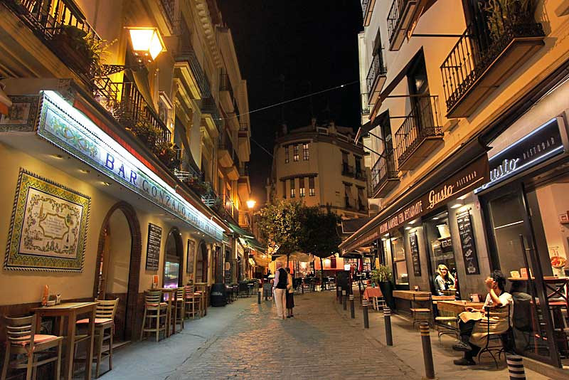 Restaurants and shops get lively at night in the center of Seville
