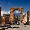 Honorary Arch in the ruins of Pompeii, Italy, frames the blown-off top of Mount Vesuvius, which erupted in 79 AD and buried the town under tons of volcanic ash