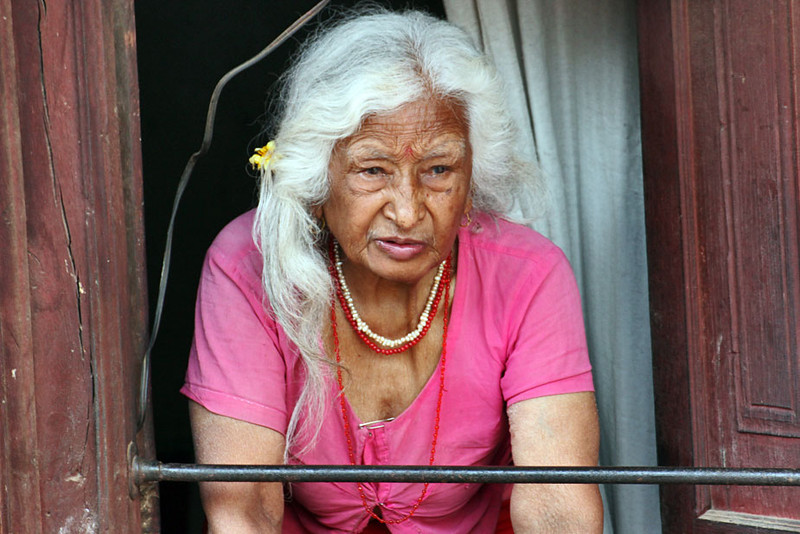 Nepali woman watches New Year festivities from her second floor window in Bhaktapur, Nepal