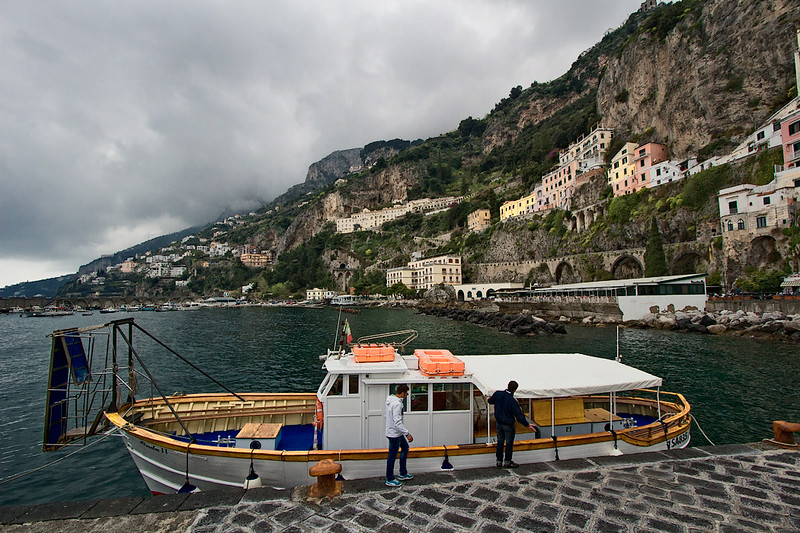 Pastel houses tucked beneath cliffs watch over the harbor at Amalfi, a town in the province of Salerno, Italy