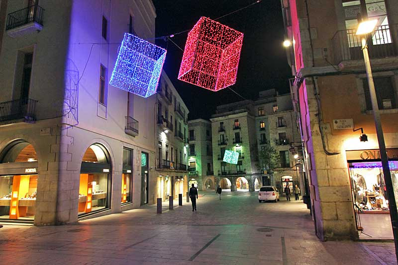 Modern Christmas decorations hang above a pedestrian shopping street in the Old Town of Girona, Spain