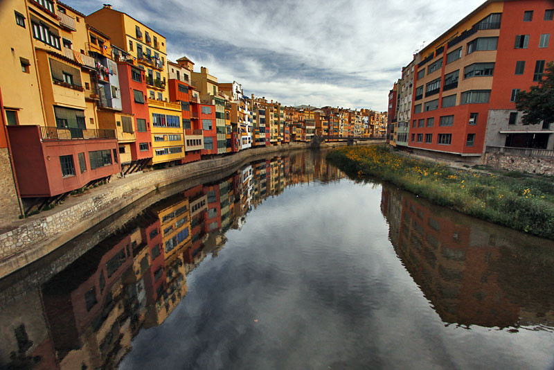 Lovely old houses in Girona, Spain reflect in the Onyar River