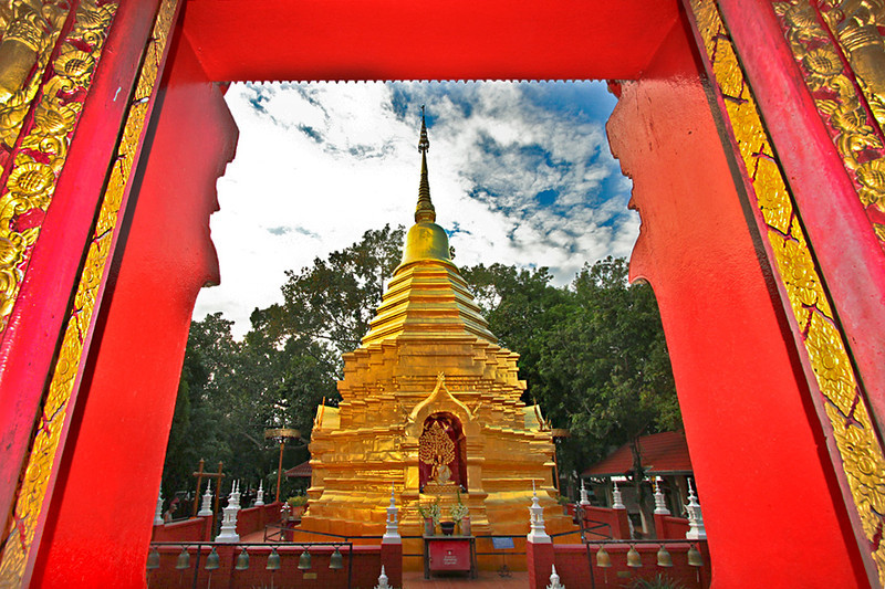 Golden Chedi at Wat Phan On in Chiang Mai, Thailand, seen through the window of the prayer hall