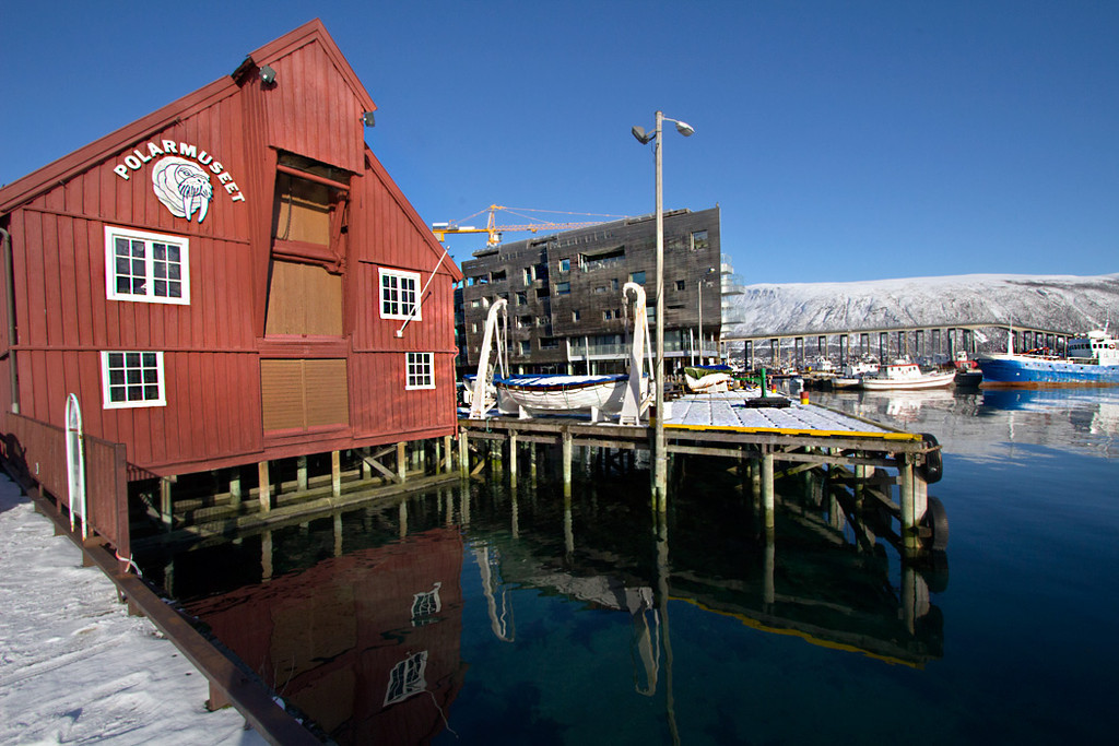 Polar Museum in Tromso Norway reflects into still waters of the Norwegian Sea