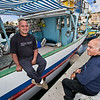 Local men take a break from the Sunday market in Marsaxlokk, on the island of Malta