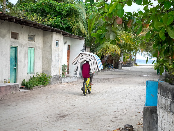 At the end of the day, local youngsters on Bodufolhudhoo Island in the Maldive Islands gather beach mats used by tourists