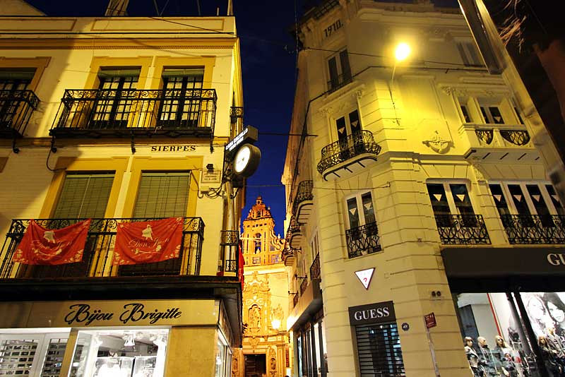 Church peeks through buildings in this typical night street scene in Seville, Spain