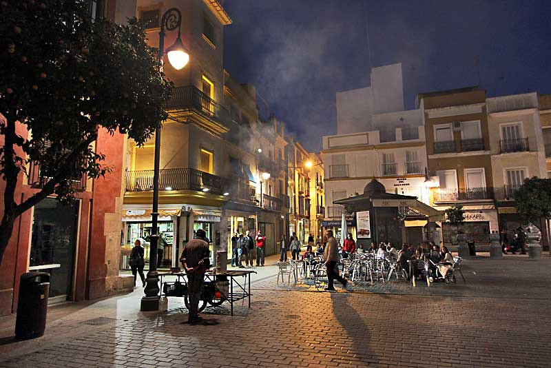 Steam rises from street vendor roasting chestnuts at Plaza del Salvador in Seville, Spain