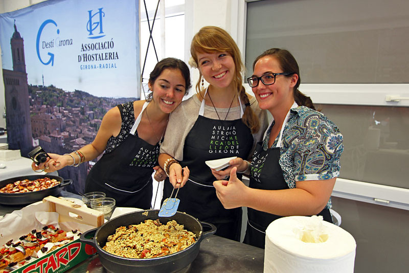 Three chefs in training in our cooking class in Girona, Spain, proudly display their vegetable Paella