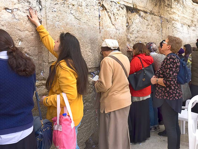 Worshipers at Western Wall in Jerusalem pray and stuff prayer-filled notes into cracks in the wall