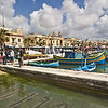 The Sunday Market in Marsaxlokk on the island of Malta stretches along the waterfront, where colorful fishing boats are anchored
