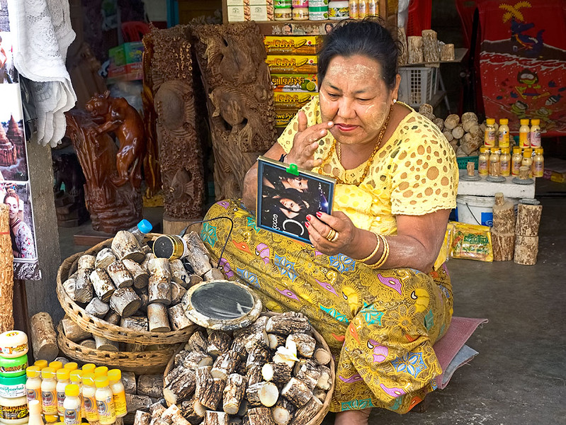 Shop owner at the Scott Market in Yangon, Myanmar, applies traditional Thanakha paste to her face. Made by grinding branches of the Thanakha tree into a powder and then adding water, the paste is used as a protection from the sun and as an enhancement to beauty