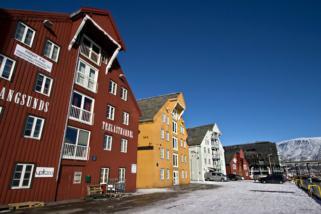 Colorful buildings on the harbor in Tromso, Norway enliven a snowy landscape