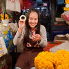 Girl at the night flower market in Chiang Mai, Thailand weaves buds into prayer offerings