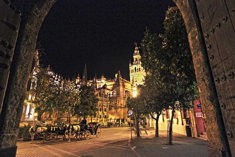 Cathedral Square in Seville, Spain is bathed in golden light at night