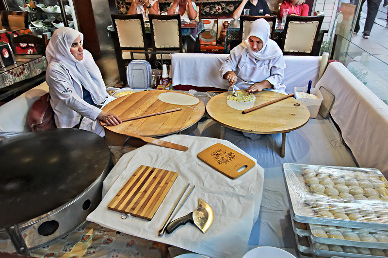 Women seated in the front window of this Istanbul restaurant make fresh breads