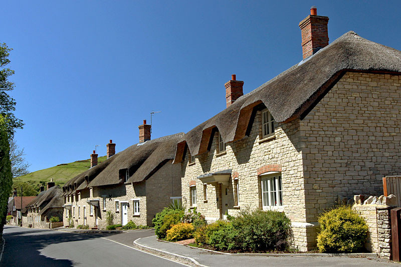 Thick thatch roofs on stone cottages in Lulworth Cove, England are protected and cannot be changed