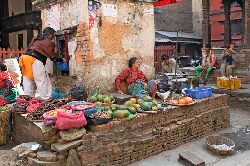 Vegetable seller displays her wares around an old building in Kathmandu, Nepal