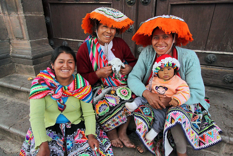 Indigenous Quichua family poses for photo on steps of a church in Cusco, Peru