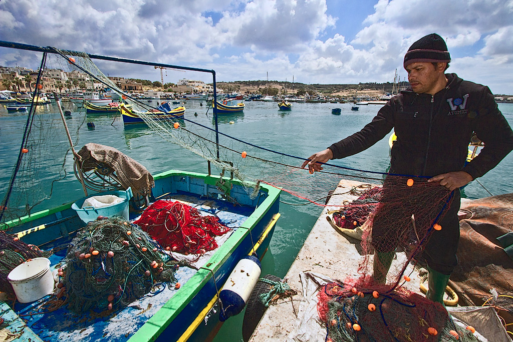 Fisherman in the village of Marsaxlokk, Malta inspects his nets after bringing in the day's catch