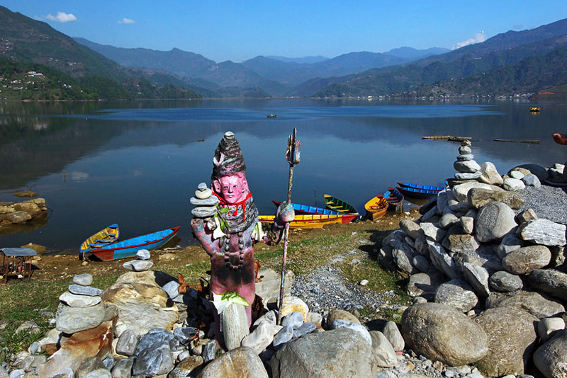 Religious icons and statues adorn the shores of Phewa Lake in Pokhara, Nepal