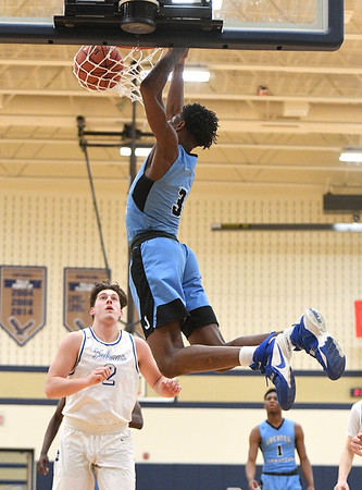 Johnstown's Dwayne Jones scores on an alley-oop pass as Lower Dauphin defender Will Bowen (2) looks on during Tuesday's 2019 PIAA Basketball playoffs at Bald Eagle High School in Wingate, Pa. Lower Dauphin defeated Johnstown, 51-30. (Photo by Steve Manuel)