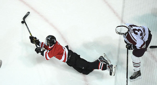 Central Cambria's Dylan Bloom (left) dives for the puck as State College's William Kerber looks on during Tuesday's PIAA Championship hockey game at Pegula Ice Arena in State College.  State College defeated Central Cambria, 5-3.  (Photo by Steve Manuel)