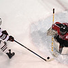 Central Cambria goaltender Alexander Nanni stops a shot on goal by State College's Joseph Semetkoskey (left) during Tuesday's PIAA Championship hockey game at Pegula Ice Arena in State College.  State College defeated Central Cambria, 5-3.  (Photo by Steve Manuel)