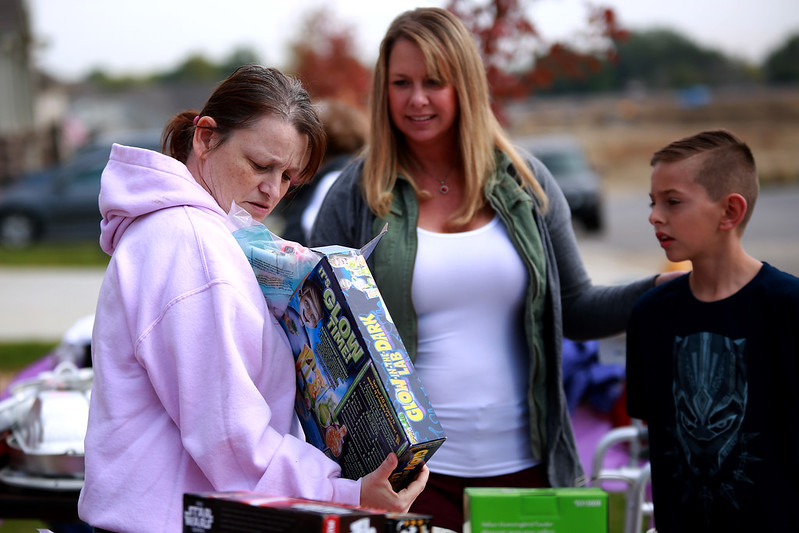 Susan Kaczmarek examines an item at her home in Berthoud as Shasta and Conner Tejeda attend a yard sale on Sept. 29, 2018 for Kaczmarek's son, Dakota Haas, who is recovering from a traumatic brain injury due to an accident involving an RV.<br /> Photo by Taelyn Livingston/ Loveland Reporter-Herald