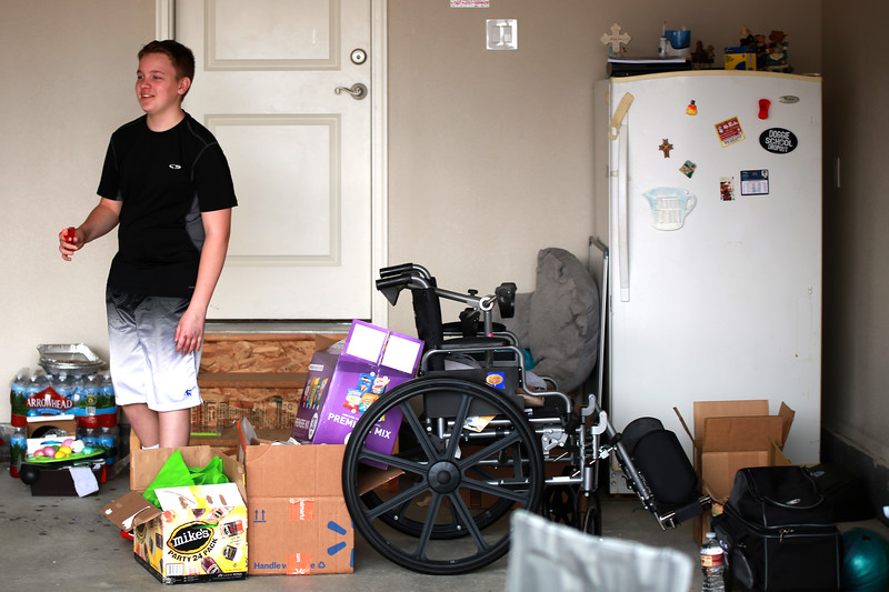 On Sept. 29, 2018 in Berthoud Dakota Haas holds a squirt gun as he stands next to his no longer needed wheel chair during his yard sale to raise money for meidcial bills after an accident he got into where he suffered from a traumatic brain injury.<br /> Photo by Taelyn Livingston/ Loveland Reporter-Herald
