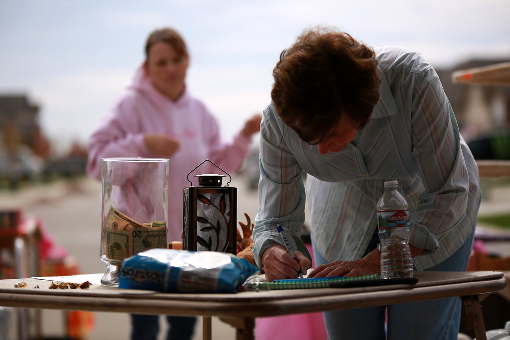 . Susan Adams writes a check on Sept. 29, 2018 in Berthoud at a yard sale for Dakota Haas that his mother, family and friends hosted in order to raise money for medical bills that were the result of a traumatic brain injury that Haas recieved after an accident with an RV. Photo by Taelyn Livingston/ Loveland Reporter-Herald