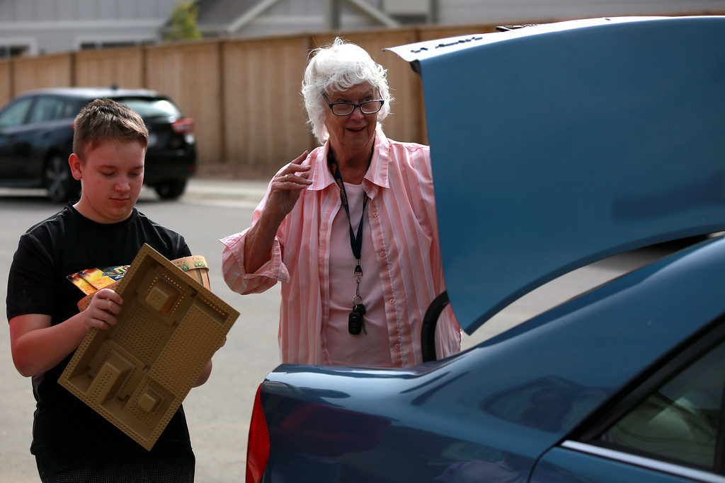 . On Sept. 29, 2018 in Berthoud, Dakota Haas accepts a donation from Alice Orswell at his yard sale that him and his family hosted in order to raise money for medical bills that were the result of a traumatic brain injury that Haas received after an accident with an RV.