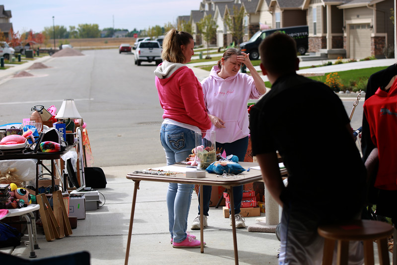 Dakota Haas leans over as Stacie Drake (left) and  Susan Kaczmarek organize the yard sale they are hosting in order to raise money for Haas's medical bills from an accident in which he suffered from a traumatic brain injury.<br /> Photo by Taelyn Livingston/ Loveland Reporter-Herald