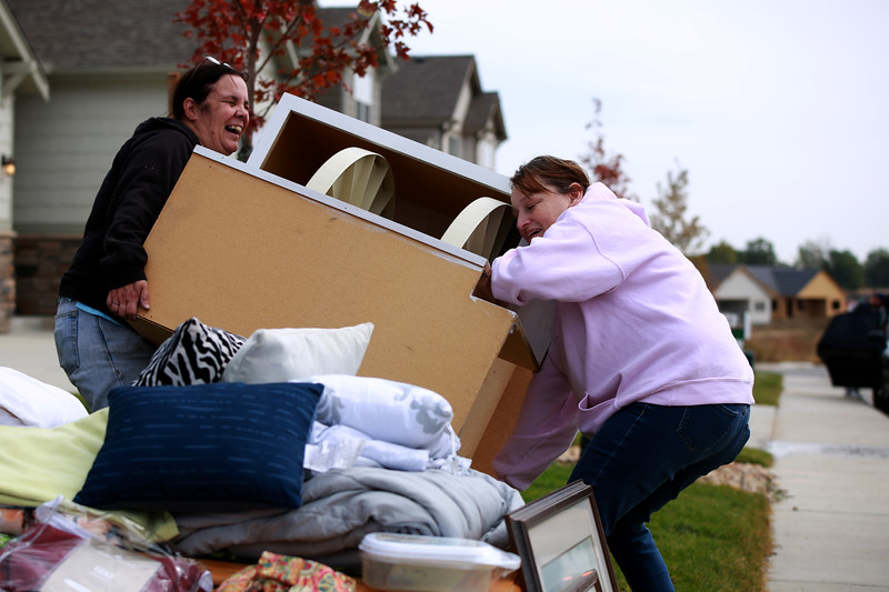 Deb Kilde (left) helps her friend Susan Kaczmarek unload an item he donated at a yard sale in order to help pay medical bills for Kaczmarek's son, Dakota Haas, who is recovering from a brain injury.<br /> Photo by Taelyn Livingston/ Loveland Reporter-Herald