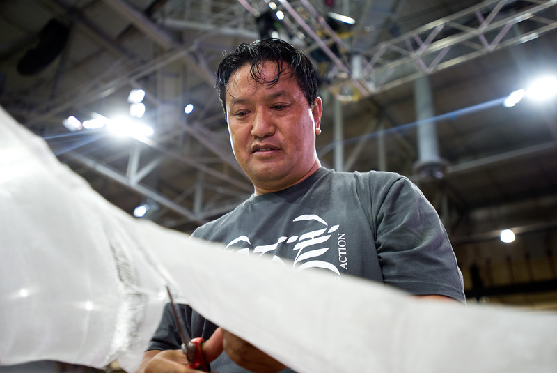 "Jawo Tashi, with the Tibetan Association of Colorado, cuts sheer fabric to be used to decorate a chair for the Dalai Lama during his visit, in the Coors Event Center at CU Boulder on Wednesday.<br /> More photos:  <a href=""http://www.dailycamera.com"">http://www.dailycamera.com</a><br /> (Autumn Parry/Staff Photographer)<br /> June 22, 2016"
