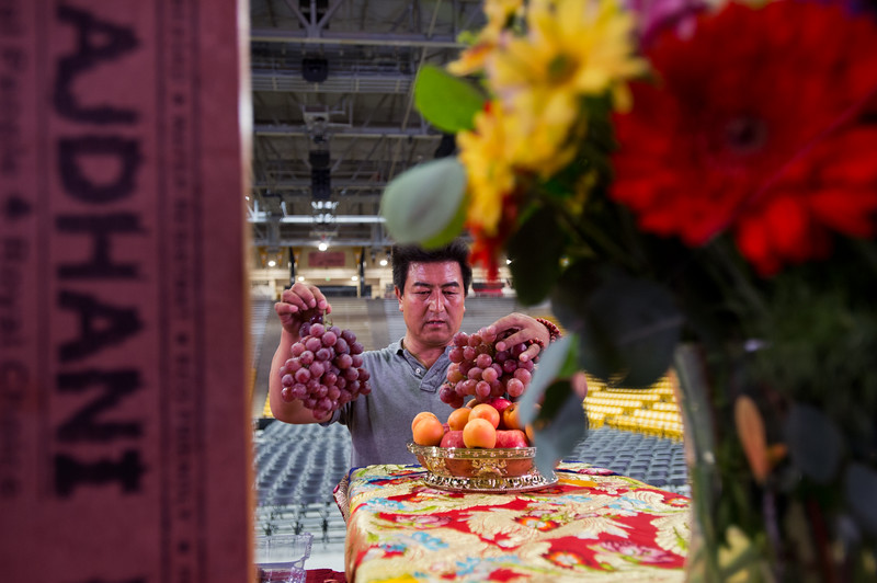 "Amdo Nyima rearranges fruit as he helps the Tibetan Association of Colorado prepare for the Dalai Lama's visit in the Coors Event Center at CU Boulder on Wednesday. <br /> More photos:  <a href=""http://www.dailycamera.com"">http://www.dailycamera.com</a><br /> (Autumn Parry/Staff Photographer)<br /> June 22, 2016"