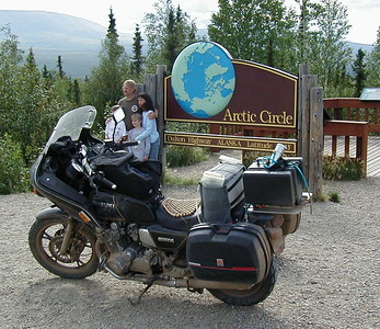 7/29/04 6:33 PM - As a family crowds together to have their photo taken in front of the Arctic Circle sign, the faithful '82 Suzuki GS1100G sits patiently waiting for me to take her on north, to collect considerably more mud on every surface before we find a car wash in Fairbanks two days hence.