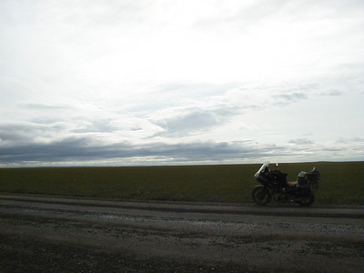 7/30/04 5:39 PM - Looking west across the Arctic coastal plain, one barely discernible rise appears just over the back end of the motorcycle - seemingly the only interruption to the pool table-like flatness of this area.