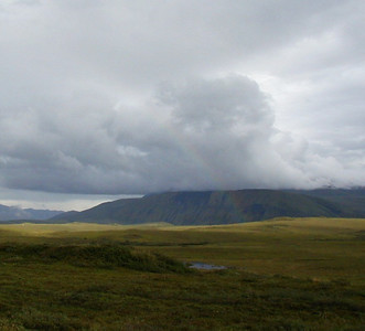 7/30/04 8:28 PM - Approaching the Atigun River valley, a faint rainbow appears over the tundra as soft rain continues to fall on the north side of the Brooks Range mountains.