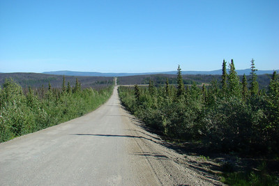 Looking north from around Mile 18.  Straight ahead is the old highway, abandoned in 2004.  The by-pass curves to the right and, while avoiding steep hills, crosses swampy stretches that are now pavement breaks, potholes and roller coaster bumps.