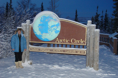 "12/24/07  10:47 - Cousin Linda - all 90 lbs of her, bundled up in a down parka with a lynx ruff, strikes a typical tourist pose next to the Arctic Circle sign, earning her the coveted ""Arctic Circle Crosser"" certificate."